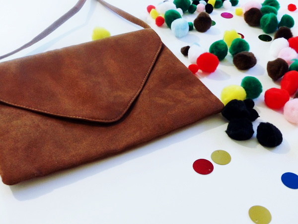suede purse and pom poms scattered